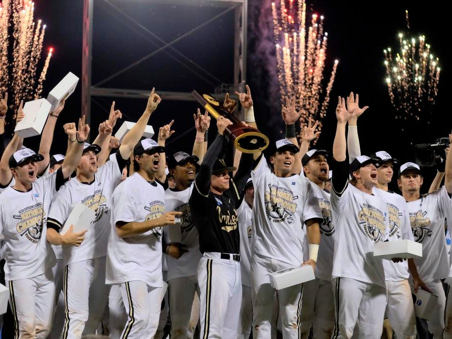 Vanderbilt coach Tim Corbin holds the trophy as he celebrates with his players after Vanderbilt defeated Virginia 3-2 in the deciding game of the best-of-three NCAA baseball College World Series finals in Omaha, Neb., Wednesday, June 25, 2014. (AP Photo/Eric Francis)