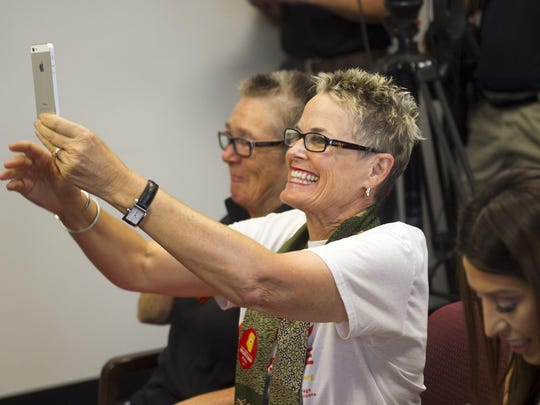 Debra Peevey, of Surprise, react as Arizona Attorney General Tom Horne announces that it is futile to continue to ban same sex marriages in Arizona, during a press conference at the Arizona Attorney General's office in Phoenix on Friday, October 17, 2014. Peevey was married to Candy Cox (background), also of Surprise in California in 2008.