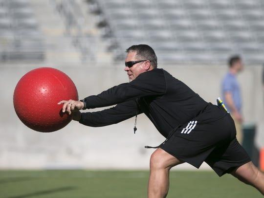 ASU special teams coordinator Shawn Slocum throws a
