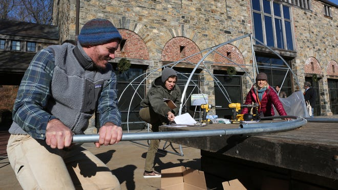Billy McCarthy bends a metal pipe used in the construction of a movable greenhouse. He was participating in a workshop during the 7th annual Young Farmers Conference at Stone Barns Center on Dec. 4.
