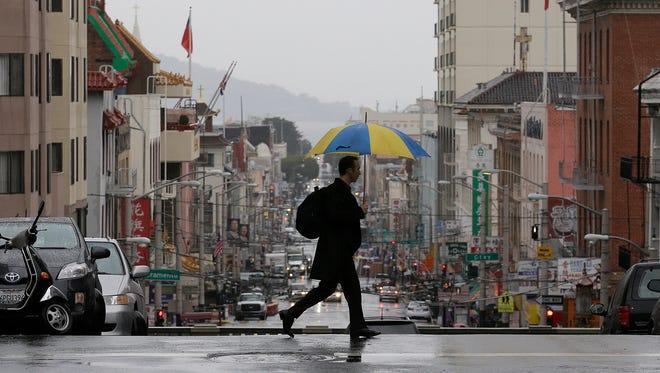 A man crosses Stockton Street in San Francisco, on Wednesday, Feb. 26, 2014.