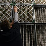Ross Feldpausch, a maintenance mechanic, works on switching out the 100 old box air filters from the building's air supply system at the Joint Operations Building in Lansing. Maintenance workers switch the filters out twice a year - once in the year and once in fall. There are about 100 box filters and about 70 bag filters.