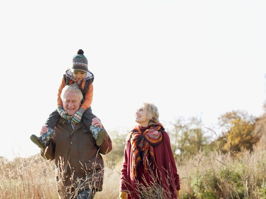 Grandparents walking outdoors with grandson