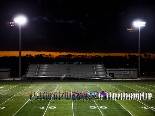 Both teams line up for the National Anthem during the Class 4A state semifinal against Forest Hill Community High School on Saturday, February 17, 2018 at Gulf Coast High School.