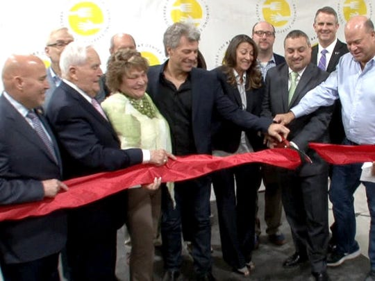 Jon Bon Jovi and his wife Dorothea help to cut the ribbon to open the new BEAT Center in Toms River, NJ, Tuesday, May 10, 2016. The BEAT Center includes a community resource and food pantry along with the JBJ Soul Kitchen