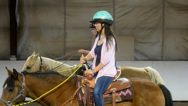 Rocky Mountain Treatment Center client Adrien Delesha participates in a therapy session at Eagle Mount riding center July 22.