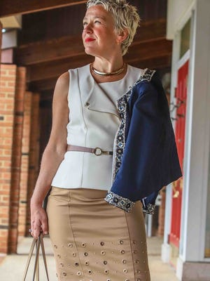 Susan Sotiropoulos wears a cropped navy jacket, cropped cream moto top, caramel woven pencil skirt and tan patent leather Mary Jane platform shoes, all from White House, Black Market.
