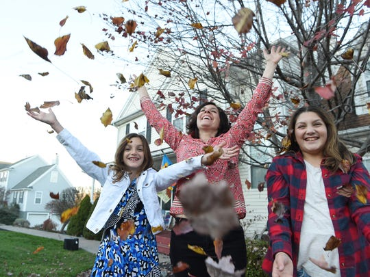 Lucille Grippo, 45, center, throws leaves up in the air with children Audrey, 8, left, and Mia, 11, right, outside of their Poughquag home. This is a tradition the Grippo family does each year during the fall. In June, Lucille lost her pulse for 35 minutes. She has recovered with minimal repercussions. Not pictured is son Nicholas, 14, and husband Patrick Grippo, 43.