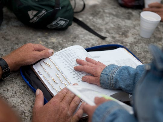 """Denise Rudisal, of Fort Pierce, (right) reads a passage from the Bible with assistance from Geo Kohler, of Fort Pierce, during a daily gathering of the Bridge Club on Tuesday, Dec. 20, 2016 at the foot of the west end of the South Bridge in Fort Pierce. Rudisal brings food and leads devotion at the Bridge Club daily. """"It's been such an amazing journey, it's been incredible,"""" Rudisal said of the Bridge Club daily meetings. """"The Lord is doing something in Fort Pierce."""""""