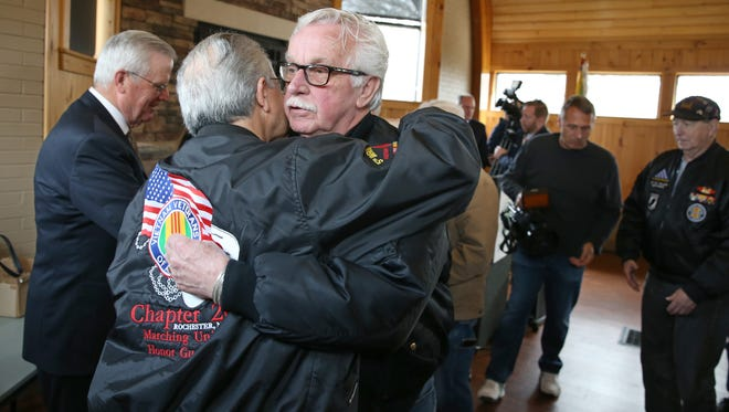 """Valentino Gatto, Vietnam Veterans of America Chapter 20 president, left, gives a hug to fellow veteran Ken Moore, Hilton, following Monroe County's annual """"Welcome Home Vietnam Veterans Day"""" ceremony Wednesday, March 29, 2017, at Highland Park."""