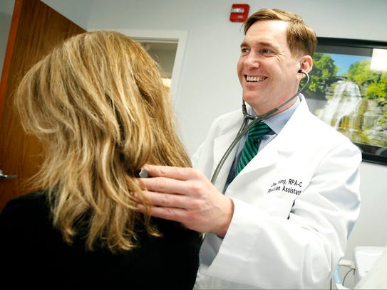 Physician assistant Jim Young demonstrates how he listens