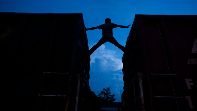 A Central American migrant practices scaling parked boxcars June 19 as he awaits the arrival of a northbound freight train in Arriaga, Chiapas state, Mexico. The number of unaccompanied minors detained on the U.S. border has more than tripled since 2011, and hundreds of immigrant families who have illegally crossed the border into Texas will be taken to Southern California Tuesday