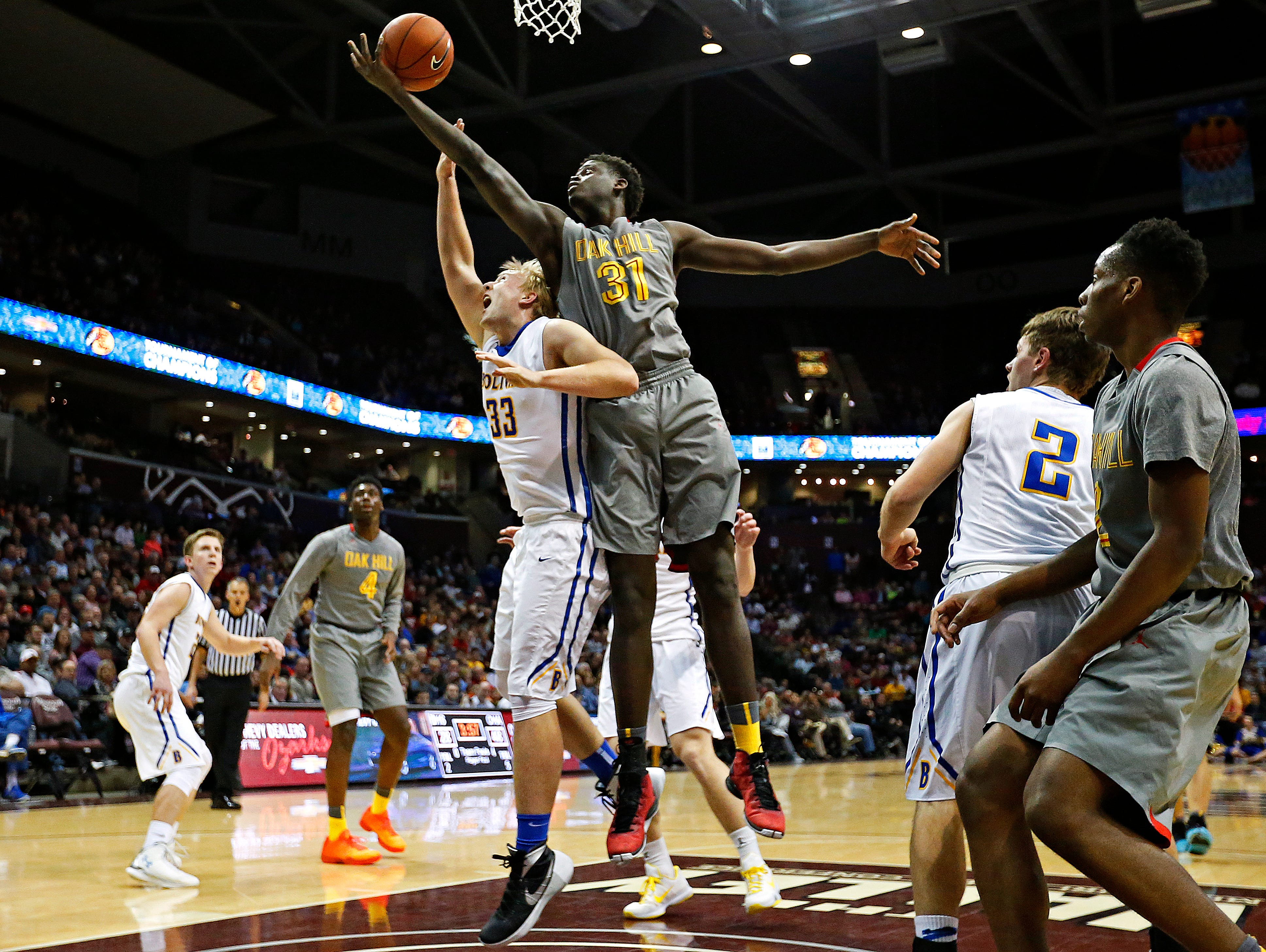Oak Hill Academy center Khadim Sy (31) grabs a rebound over Bolivar High School forward Brandon Emmert (33) during third quarter action of the 2016 Tournament of Champions first round game between Bolivar High School (Bolivar, Mo.) and Oak Hill Academy (Mouth of Wilson, Va.) at JQH Arena in Springfield, Mo. on Jan. 14, 2015. The Oak Hill Warriors won the game 73-38.