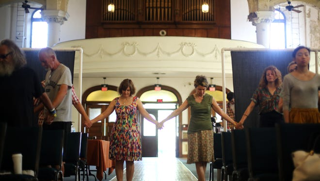 Churchgoers pray at Vineyard Central at the old St. Elizabeth Church in Norwood in September. A recent poll indicated unchurched Christians are more concerned about poverty and income inequality as an issue in the upcoming election.