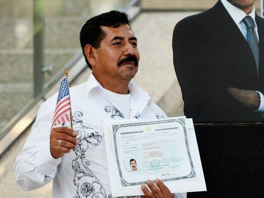 Angel Garcia Palacios sostiene su certificado de naturalización