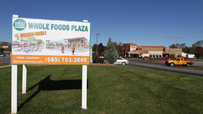 A sign advertises the proposed Whole Foods Center on Monroe Avenue, with the former Mario's restaurant in the background.