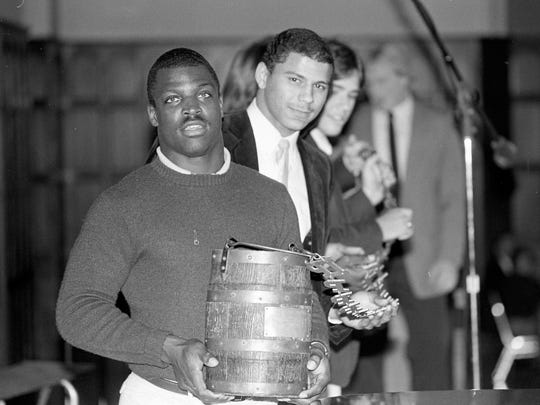 In this 1983 file photo, sophomore running back Lloyd Hawthorne and freshman safety Rod Woodson hoist the spoils from the annual gridiron battle against Indiana for the Old Oaken Bucket.