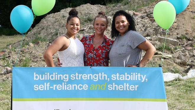 Shanon Longaberger, center, and her daughters, Brooklyn Campbell, 14, left, and Nautica Longaberger, 21, right, pose in front of a large mound of dirt where their Alliance Area Habitat for Humanity home will be built on Noble Street. The family celebrated with a double groundbreaking ceremonyThursday.
