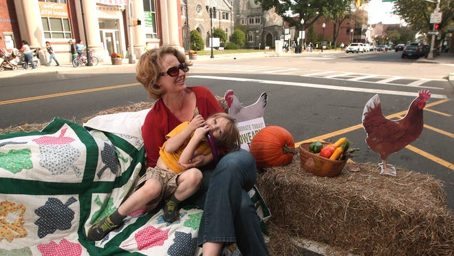 Grow It Green Morristown President Samantha Rothman and son, Ezra, 3, relax on hay bales as South Street parking spots are turned into a PARK(ing) Space, kicking off its communitywide 'Grow Early' capital campaign  on Friday in Morristown.
