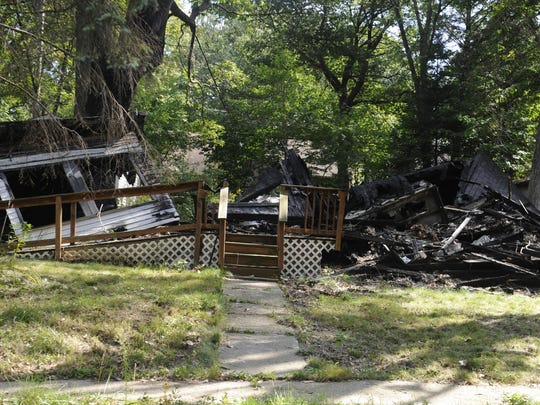 In a remote spot in northwest Detroit along the Rouge River, neighbors are recruiting a squatter to occupy a home whose longtime owners left last weekend. Eight nearby houses burned in the past two years, including this one on Hazelton.