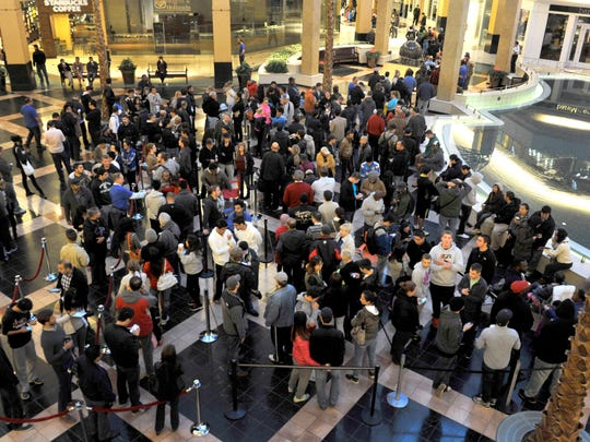 Hundreds wait in line at the Apple Store at Somerset Collection Friday.
