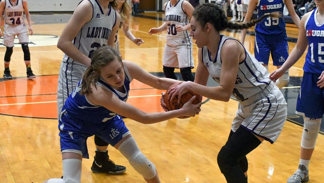 Athens' Corra Hamilton (4) battles with Lenawee defender Taegan Long (33) for a loose ball during the first quarter of play Tuesday night.