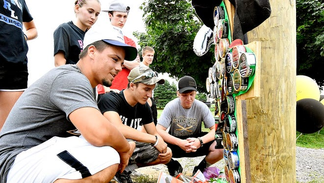 From left, Red Lion-area residents Dylan Gurreri, Cody Stern and Cody Heffner gather around a memorial built at the base of a utility pole on Slab Road for their friends and classmates Stone Hill, 17, of Delta, and Nicholas Mankin, 16, of Felton, the day after the two Red Lion students died in a fiery crash. (Dawn J. Sagert photo - dsagert@yorkdispatch.com)