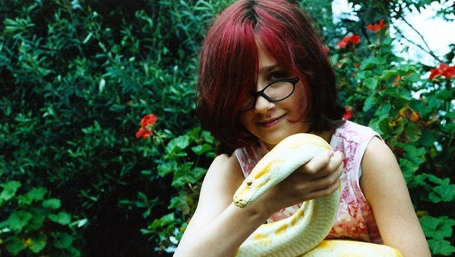 Madison Lattanzi holds Buttercup, a 13' Burmese python and one of the stars of Creature Feature.