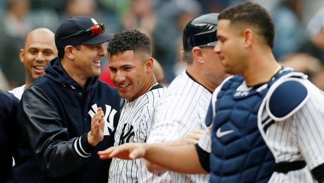 New York Yankees manager Aaron Boone, left, congratulates Gleyber Torres, second from left, after Torres hit a ninth-inning, walk-off, three- run, home run in a baseball game against the Cleveland Indians in New York, Sunday, May 6, 2018. Yankees catcher Gary Sanchez is at right. The Yankees won 7-4.