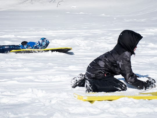 Sawyer Thomas, 5, left, sleds past his brother, Corbin,