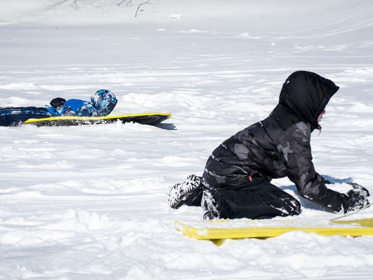 Sawyer Thomas, 5, left, sleds past his brother, Corbin, 9, at the sledding hill at the Palmer Park Recreation Center Monday. Both kids, who attend Garfield Elementary, were given a snow day.