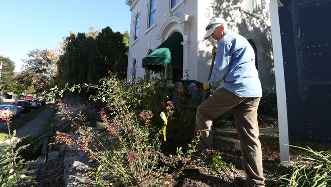 Mark Dwertman works on the landscape outside of the Baker Hunt Art and Cultural Center on Greenup Street in Covington Wednesday October 14, 2015. Baker Hunt is planning major renovations of its four-building campus which also includes a garden. The problem right now is, the city of Covington said plans specifically for a glassed-in garden center and a main entry into the grounds do not comply with historic guidelines for the area.