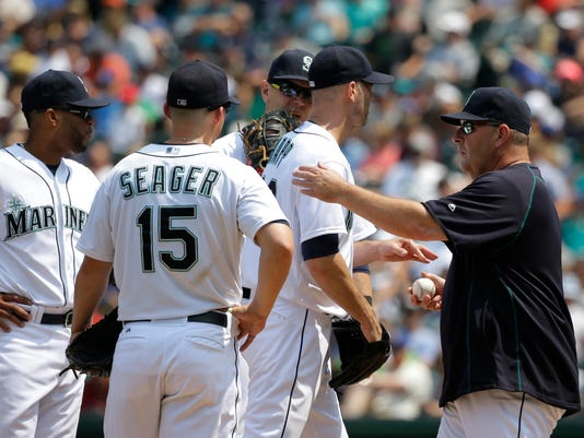 Seattle Mariners starting pitcher J.A. Happ, second from right, is pulled in the fifth inning of a baseball game against the Detroit Tigers by Mariners bench coach Trent Jewett, right, who was handling managing duties in the absence of Mariners manager Lloyd McClendon, Wednesday, July 8, 2015, in Seattle. (AP Photo/Ted S. Warren)