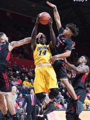 Iowa Hawkeyes guard Peter Jok (14) shoots while being defend by Rutgers Scarlet Knights guard Bishop Daniels (2) and Rutgers Scarlet Knights guard Corey Sanders (3)  in the first half at Louis Brown Athletic Center.