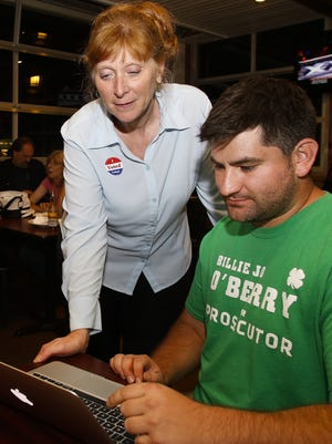 Republican candidate for Ingham County Prosecutor, Billie Jo O'Berry, watches votes trickle in Aug. 2 with campaign volunteer Kip O. Legate, right, at City Limits Sports Bar in Mason.