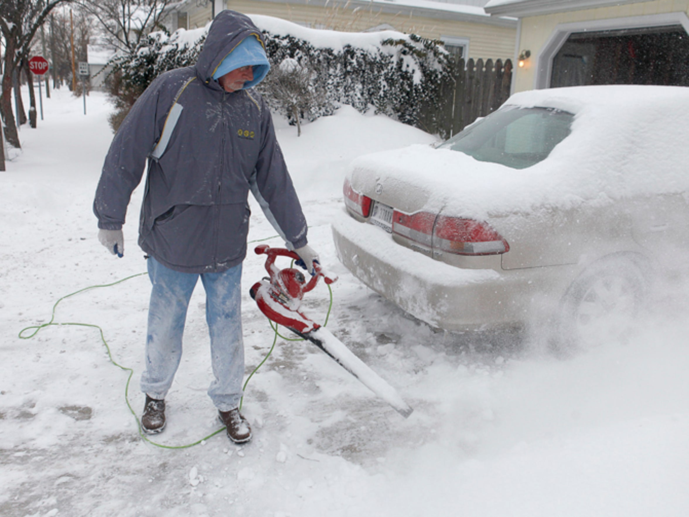 Darrell Hughes uses a leaf blower to clear snow from