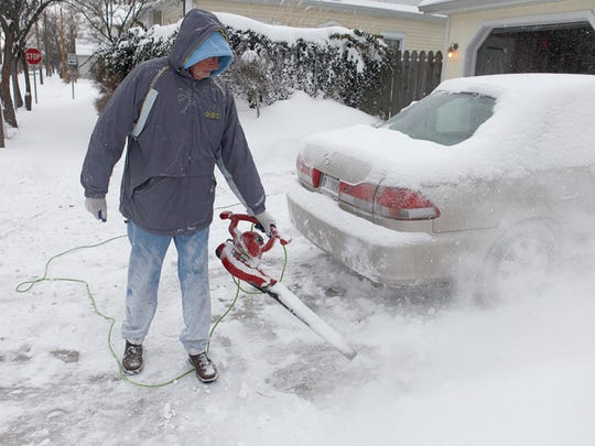 Darrell Hughes uses a leaf blower to clear snow from his driveway in Muncie Sunday morning. Hughes said the leaf blower is one of the best snow removal tools he's had.