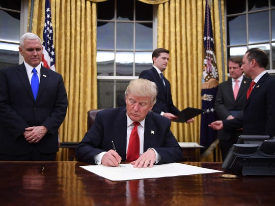 President Donald Trump signs a confirmation for John Kelly as U.S. Secretary of Homeland Security shortly after the inauguration Friday, Jan. 20, as Vice President Mike Pence (L) and White House Chief of Staff Reince Priebus look on, in the Oval Office of the White House. (Jim Watson/AFP/Getty Images)