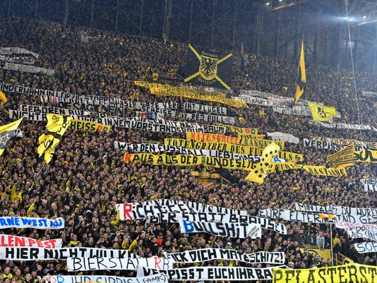 FILE - In this Feb. 4, 2017 file photo Dortmund's supporters on the southern tribune protest against the Red Bull owned RB Leipzig club prior the German Bundesliga soccer match between Borussia Dortmund and RB Leipzig in Dortmund, Germany. The German Soccer Federation Sports court has ordered Dortmund to close the southern tribune for one home match and a fine of 100,000 euros because of clashes during the match versus Leipzig.  (AP Photo/Martin Meissner)