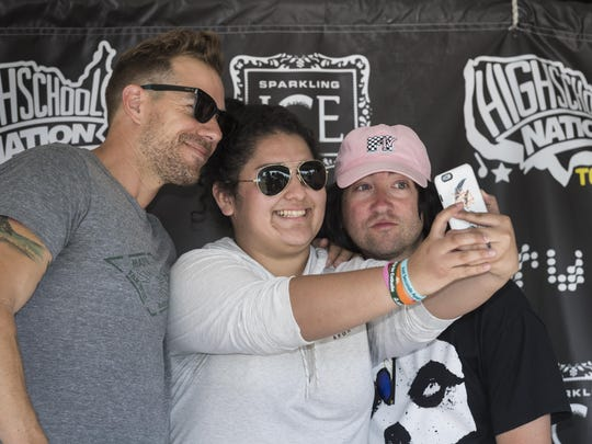 Exeter High School senior Ariana Velasquez takes a selfie with Plain White T's band members Tim G. Lopez, left, and Tom Higgenson after a last-minute concert Wednesday. Students made t-shirts, painted vinyl albums and listened to several bands.