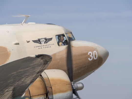 """Co-pilot Travis Major looks out from the cockpit of """"Old Number 30,"""" a WWII Douglas C-47A, as it arrives at Visalia Municipal Airport on Wednesday, May 10, 2017. The aircraft completed thousands of missions in different capacities beginning in April of 1943. Tours are $2 per person or $5 for a family of four. A limited number of rides are available at $150 per person."""