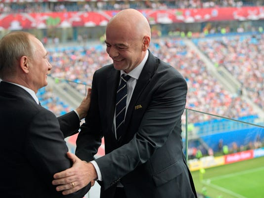 FILE- In this Saturday, June 17, 2017 file photo, Russian President Vladimir Putin, left, and FIFA President Gianni Infantino shake hands during the Confederations Cup, Group A soccer match between Russia and New Zealand, at the St. Petersburg Stadium, in St. Petersburg, Russia. When FIFA's Gianni Infantino sat with Russian President Vladimir Putin at the opening game June 17, the host nation was under a cloud, facing pressure over widespread doping in multiple, fan racism and a reported 17 deaths during construction of World Cup stadiums. (Alexei Druzhinin/Sputnik, Kremlin Pool File Photo via AP)