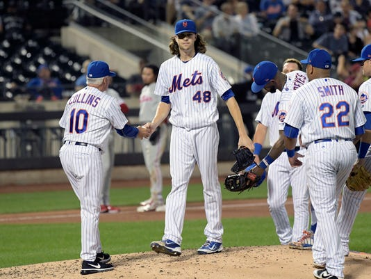 New York Mets pitcher Jacob deGrom (48) hands the ball to manager Terry Collins (10) as deGrom leaves the baseball game during the fourth inning against the Philadelphia Phillies Tuesday, Sept. 5, 2017, at Citi Field in New York. (AP Photo/Bill Kostroun)