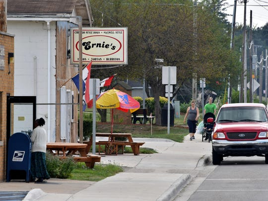 Pedestrians stroll down the sidewalk past Ernie's, a popular Hispanic-owned eatery next to the U.S. Post Office in Covert near South Haven late last month.