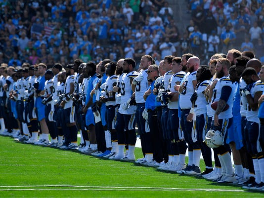 The Los Angeles Chargers lock arms during the playing of the national anthem before an NFL football game against the Philadelphia Eagles, Sunday, Oct. 1, 2017, in Carson, Calif. (AP Photo/Mark J. Terrill)