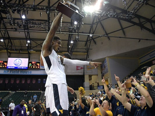 West Virginia guard Daxter Miles Jr. (4) shows the championship trophy to fans after earning a 83-79 win over Missouri in an NCAA college basketball championship game at the AdvoCare Invitational tournament Monday, Nov. 27, 2017, in Lake Buena Vista, Fla. (AP Photo/Phelan M. Ebenhack)