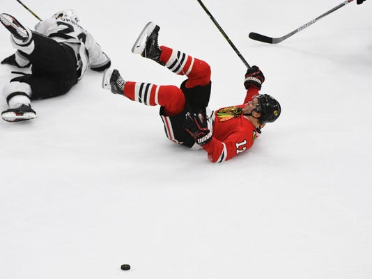 Chicago Blackhawks left wing Lance Bouma (17) and Los Angeles Kings defenseman Derek Forbort (24) lie on the ice after reaching for the puck during the second period of an NHL hockey game Sunday Dec. 3, 2017, in Chicago. (AP Photo/Matt Marton)