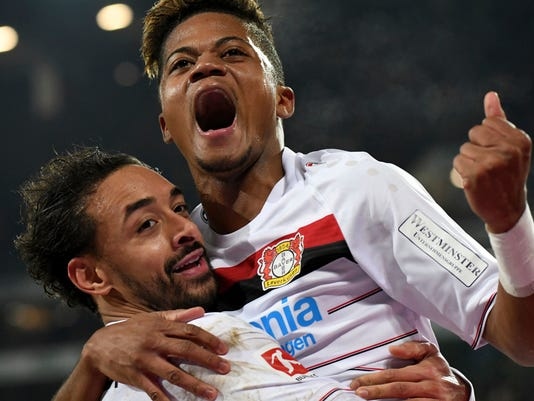 FILE - In this Dec. 17, 2017 file photo Leverkusen's Leon Bailey. top, celebrating a goal with teammate Karim Bellarabi during the German Bundesliga soccer match between Hannover 96 and Bayer Leverkusen in Hannover, Germany.  It took some time for Leon Bailey to settle at Leverkusen after arriving from Belgian club Genk last January, but the now 20-year-old Jamaican has really shone toward the end of the year.  (Peter Steffen/dpa via AP, file)