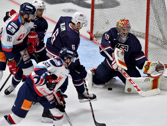 FILE - In this Nov. 10, 2017, file photo, Slovakia's Patrik Lamper, center, scores a goal in the first period of the game past Ryan Zapolski, right, goalkeeper of United States, during the Ice hockey Deutschland Cup game in Augsburg, Germany. Zapolski knows even serious hockey fans back home in North America have never heard of him. He's OK with that after spending his entire career being overlooked. Now he's the United States' best hope to medal in the men's hockey tournament without NHL players. (Peter Kneffel/dpa via AP, File)