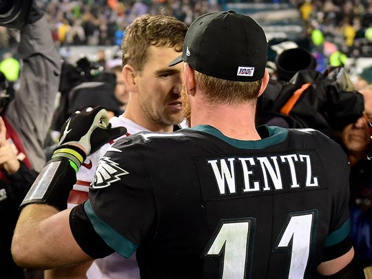 PHILADELPHIA, PENNSYLVANIA - DECEMBER 09: Quarterback Eli Manning #10 of the New York Giants and quarterback Carson Wentz #11 of the Philadelphia Eagles embrace after the overtime game at Lincoln Financial Field on December 09, 2019 in Philadelphia, Pennsylvania. The Philadelphia Eagles win 23-17. (Photo by Emilee Chinn/Getty Images)